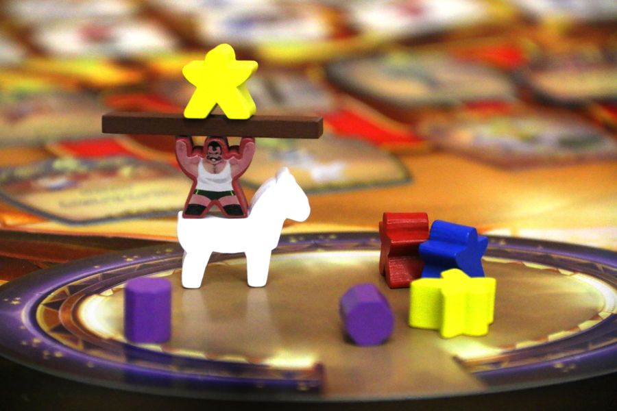 Photo showing gameplay of Meeple CIrcus. Wooden objects are stacked in a cardboad circus ring: a strongman stands on the back of a horse, lifting a plank with another performer on top.