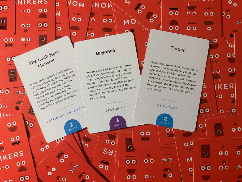 Photo showing three examples of prompt cards from the family card game Monikers: 'The Loch Ness Monster', 'Beyonce', and 'Tinder'.