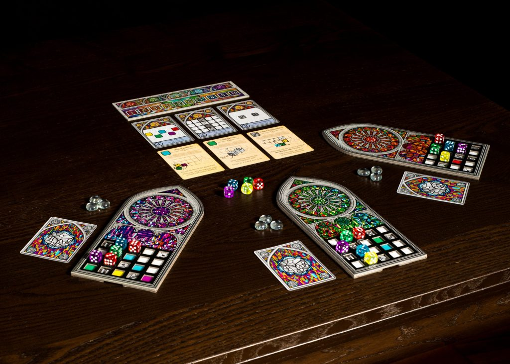 Photo showing a game of Sagrada in progress. Three boards in the shape of stained-glass cathedral windows are being covered in multicoloured dice.